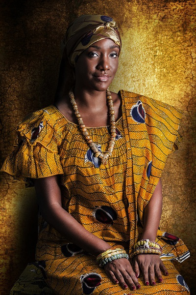 """Naéma Assassi is a Real Estate Business Developer. Her family is from the center of the Ivory Coast (Akan). Naema grew up in a multi culrural family in between Abidjan, and Bonn (Germany) where she used to spend her childhood summers with Marianne, her german paternal grandmother. According to her, a modern African woman is the perfect synthesis of African tradition and the western culture. . """"I went to the photo session with apprehension, I was nervous to be portrayed in a this traditional outfit i never wear. The clothes I was wearing belonged to my maternal grandmother. I used call her Nanou. """" Naema was shocked and moved to see the results of the photo session, as she noted her strong resemblance to Nanou"""""""